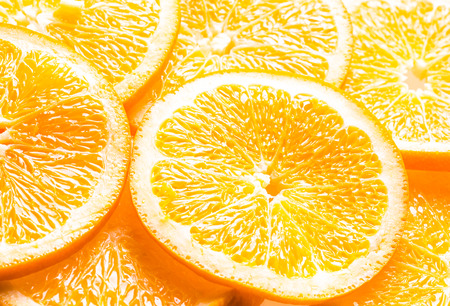 pith: Full frame background of juicy orange slices showing the texture of the pulp, pith and rind with an angled perspective