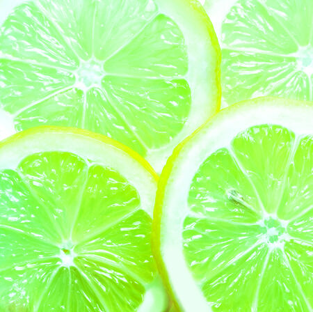 Colorful background of sliced juicy green limes rich in vitamin c with a tangy flavor used as an ingredient and garnish in cooking, full frame overhead close up view