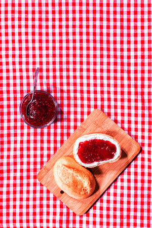 Fresh crusty roll with strawberry jam on a wooden bread board on a red and white checked rustic tablecloth with copyspace, overhead view photo