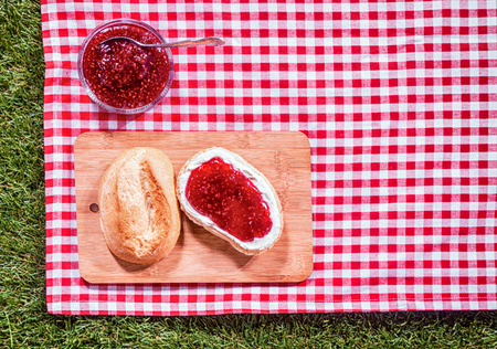 pic nic: Strawberry preserve with a fresh crusty roll on a wooden bread board on a red and white checked tablecloth spread on green grass for a summer picnic, overhead view Stock Photo