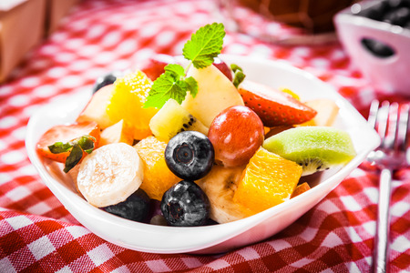 Colorful bowl of tropical fruit salad with blueberries, kiwifruit, orange, apple, banana, grapes and orange for a healthy summer picnic photo