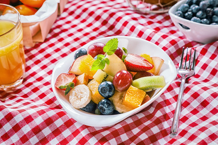 pic nic: Healthy summer picnic with fresh colorful tropical fruit salad served in a bowl on a red and white checked cloth