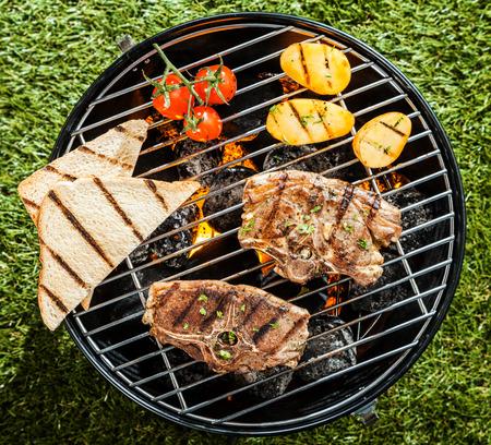 ラムチョップと夏のピクニックで芝生の上のポータブル バーベキュー立って焼き新鮮な野菜の上からの眺め