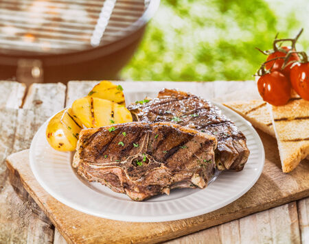 top angle: Delicious summer BBQ with a serving of grilled chops seasoned with herbs and roast potato on a plate on a rustic wooden picnic table in the garden Stock Photo