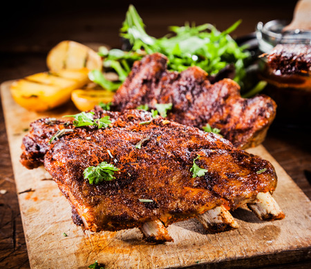 Delicious piquant grilled ribs cooked on a summer BBQ and marinated with a spicy basting sauce topped with fresh herbs and served with grilled potatoes on a wooden board