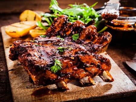 Délicieux travers de porc grillés assaisonnés avec une sauce à badigeonner épicée et servi avec des herbes fraîches hachées sur un vieux rustique planche à découper en bois dans une cuisine de campagne