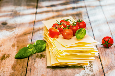 lasagna: Ingredients for Italian lasagne with fresh cherry tomatoes and green basil leaves on sheets of dried pasta on a rustic wooden kitchen table
