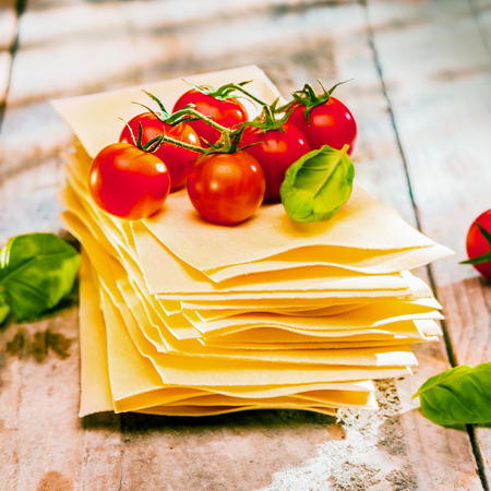 lasagna: Dried uncooked lasagne pasta sheets with fresh ingredients including cherry tomatoes and basil leaves, close up on old wooden boards