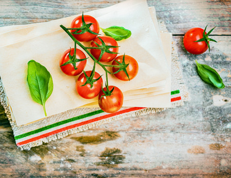 Cherry tomatoes, basil and dried lasagne sheets on an old weathered wooden table in a rustic kitchen ready to be used as ingredients for an Italian pasta dish, view from above photo