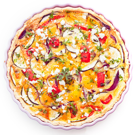 Closeup overhead view of a tasty vegetarian quiche with eggplant or brinjals, cheese, herbs, pepper and tomato in a golden pie crust for a delicious savory meal
