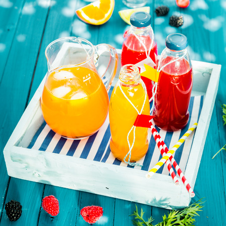 Fresh homemade orange and berry juice served in glass bottles and chilled with ice in a glass jug on a colorful, blue wooden picnic table on a wooden tray