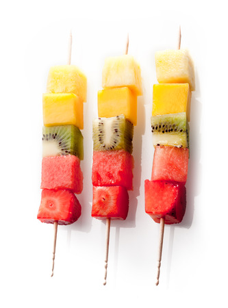 Trio of colorful, healthy fresh fruit kebabs with neatly cut cubes of exotic and tropical fruits arranged in a row on a white background Stock Photo