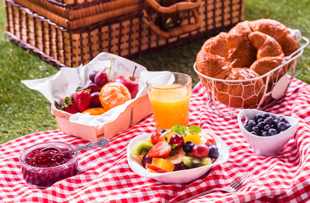 picknick: Healthy vegetarian or vegan picnic with a delicious spread of fresh fruit, golden croissants, berry jam and tropical fruit salad on a red and white tablecloth alongside a hamper on green grass Stock Photo