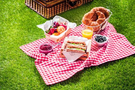 lawn party: Healthy picnic for a summer vacation with freshly baked croissants, fresh fruit and fruit salad, sandwiches and a glass of refreshing orange juice laid out on a red and white checked cloth and hamper
