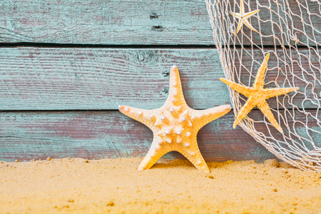 Nautical background with starfish and a fishing net against rustic weathered blue wooden planks above golden beach sand Zdjęcie Seryjne