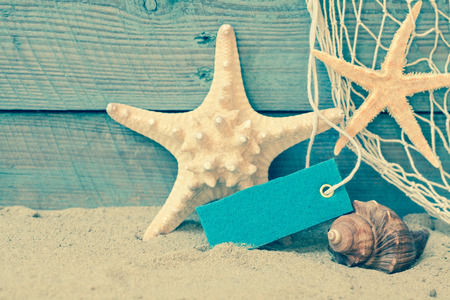 Toned retro nautical background with starfish and a seashell on beach sand against rustic blue wooden boards with a blank label or tag with copyspace and a decorative fishing net photo