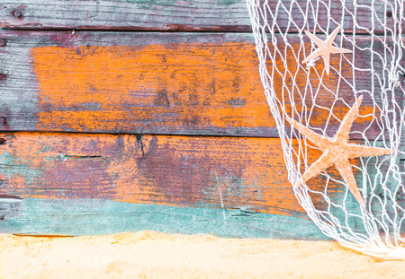 Nautical starfish background with rustic grunge weathered blue painted wooden boards, fishing net and golden beach sand, copyspace for text photo