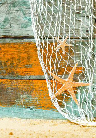 Rustic marine background with starfish suspended in a fishing net over weathered blue and orange painted wooden boards with copyspace and beach sand below photo