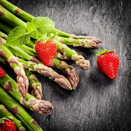 vignetting: Fresh green asparagus spears and ripe colorful red strawberries garnished with a sprig of fresh peppermont on a dar textured background with vignetting and copyspace