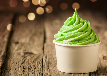 cream and green: Tub of twirling creamy green Italian ice cream on a rustic wood table with a sparkling bokeh of party lights