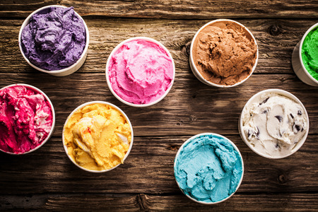 Selection of gourmet flavours of Italian ice cream in vibrant colors served in individual plastic tubs on an old rustic wooden table in an ice cream parlor, overhead view