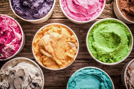 뜨거운 여름 날에 맛있는 냉동 간식 아이스크림이 오래 된 나무 테이블에 표시 플라스틱 통에 다른 맛을 낸 다채로운 아이스크림의 배열 스톡 콘텐츠