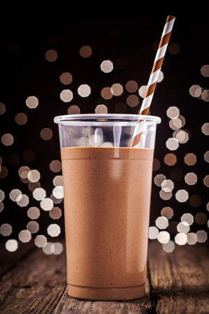 Plastic glass of delicious creamy chocolate smoothie or milkshake against a background of sparkling festive party lights photo