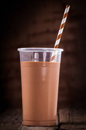 Close up of a glass of chocolate or cacao smoothie with a spiral patterned straw against a dark background photo