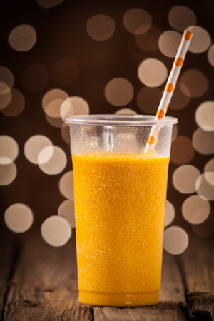 Glass of healthy refreshing cold orange mango smoothie with a straw on a wooden counter with a festive sparkling bokeh of party lights photo