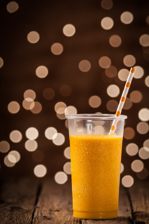 Plastic glass of tasty refreshing chilled tropical orange mango smoothie standing on a wooden counter overlooking a twinkling bokeh of party lights with copyspace photo