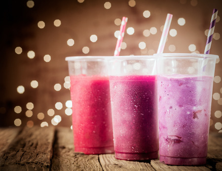 Three different colorful berry smoothies with twinkling party lights standing in a row on a rustic wooden counter top at a restaurant or bar