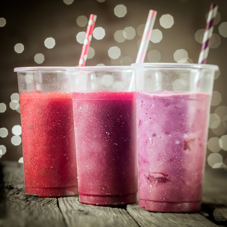 Trio of healthy assorted berry smoothies including strawberry and blueberry blended with yogurt or ice cream standing in a row against a bokeh of party lights photo