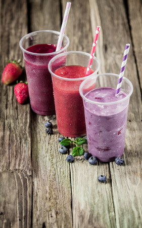 Choice of three delicious berry smoothies blended with yogurt or ice cream with fresh strawberries and blueberries, high angle view photo