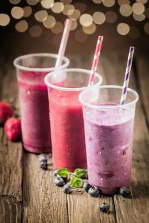 Berry smoothies with farm fresh blueberries and strawberries blended with yogurt and ice cream for a healthy summer treat with a bokeh of sparkling party lights photo