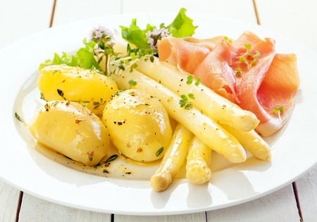 Cold asparagus spears with parma ham and boiled baby potatoes served with lettuce and chopped fresh herbs, close up view on a plate Banco de Imagens - 27129056