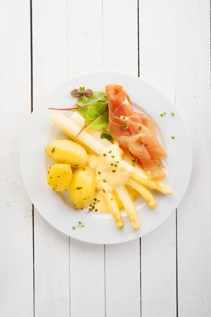 esparragos: Espárragos y parma italiano o jamón prosciutto con mayonesa servido con patatas cocidas bebé para una deliciosa comida fría de verano, vista aérea en la mesa de madera blanca con copyspace Foto de archivo