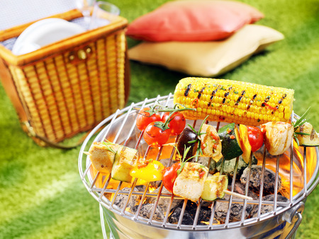Healthy halloumi kebabs grilling over a fire in a portable barbecue with tomatoes and fresh corn on the cob on a summer picnic in the garden
