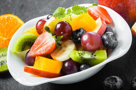 fruity salad: Colorful bowl of healthy tropical fruit salad with blueberries, strawberries, kiwifruit, banana, grape, orange for a delicious refreshing breakfast Stock Photo