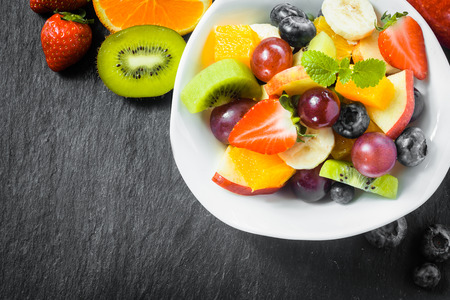 natural selection: Preparing a bowl of tasty fresh fruit salad for breakfast with tropical ingredients on a rustic slate kitchen counter, overhead view with copyspace Stock Photo