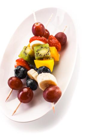 brochetas de frutas: Servir de coloridas brochetas de frutas tropicales saludables en los pinchos de madera con las uvas, plátano, naranja, kiwi y fresa en un plato blanco oval, alto ángulo vista de cerca