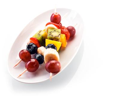 ブドウ、ブルーベリー、バナナ、オレンジ、キウイ フルーツ、イチゴは、白い背景に白い楕円皿上に添えて copyspace、高角度で新鮮な健康的なトロピ