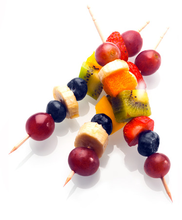 nutriment: Vibrant fresh fruit kebabs for a healthy snack with assorted grapes, strawberries, blueberries, banana, kiwifruit and orange on wooden skewers on white