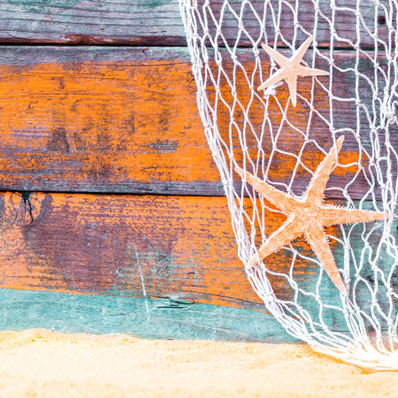 east coast: Rustic nautical background with starfish hanging in a fishing net against weathered painted wooden boards in blue and orange with copyspace over golden tropical beach sand