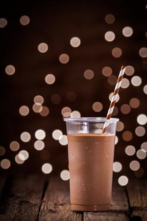 チョコレートのスムージーやレストランやバーで素朴な木製のテーブル背景に立っでパーティー ライトの光っているボケ味を持つミルクセーキ