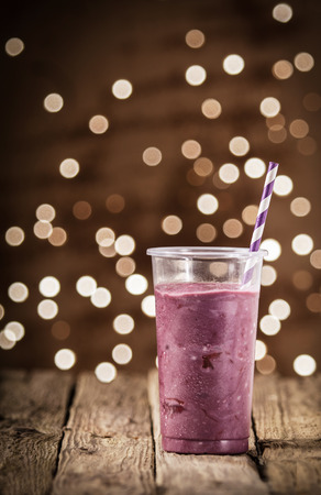 energising: Energising berry smoothie in a plastic glass with a straw standing on a rustic wooden counter at a pub or diner with a background bokeh of sparkling lights Stock Photo