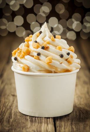 Decorative creamy party vanilla ice cream sundae twirled in a takeaway plastic tub and sprinkled with chocolate pearls and nuts with a background bokeh of party lights photo