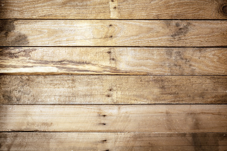 Old weathered rustic wooden background texture with vintage brown wood boards with an uneven row of nails in the centre and stained woodgrain pattern, empty with copyspace