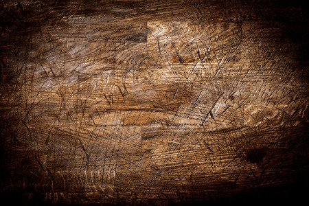 Background texture of old grungy scored wood with crisis-crossed cut marks from a knife and a heavy vignette photo