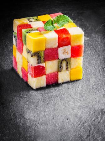 Colorful gourmet cube of diced fresh tropical fruit with watermelon, melon, orange, strawberry, banana, kiwifruit and apple garnished with mint on a slate kitchen counter with copyspace photo
