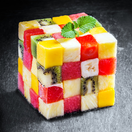 Decorative colorful cube of diced fresh summer tropical fruit composed of pineapple, watermelon, strawberry, banana, orange, strawberry and kiwifruit cut in squares for a geometric pattern photo